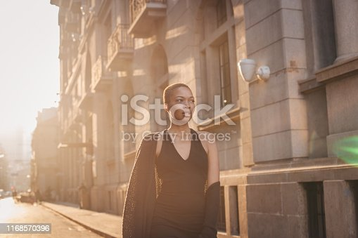 One woman in black dress, standing downtown on the street.