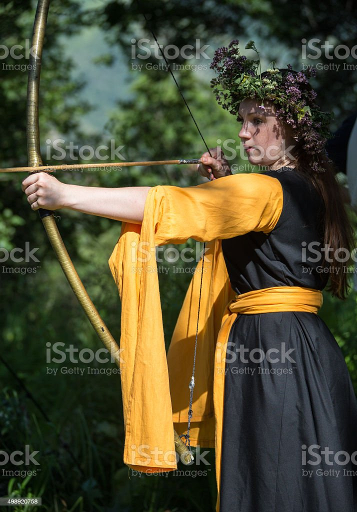 Beautiful woman drawing a bow stock photo