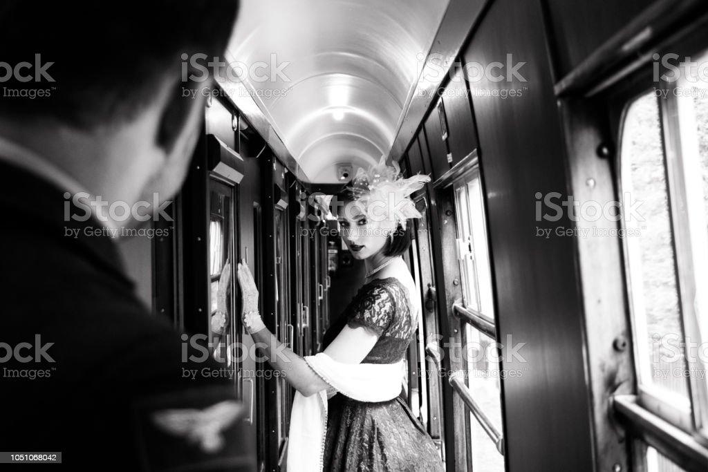 Beautiful woman dressed in red tea vintage tea dress on locomotive train stock photo