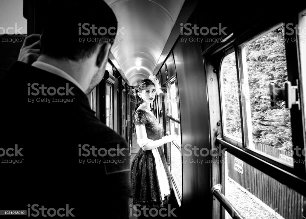 Beautiful woman dressed in red tea vintage tea dress on locomotive standing in corridor with officer watching her stock photo