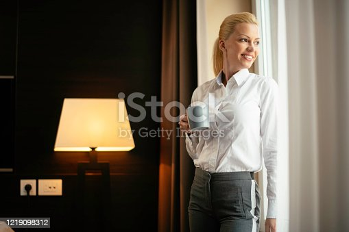 947825822 istock photo Beautiful woman drinking coffee and working in hotel room. 1219098312