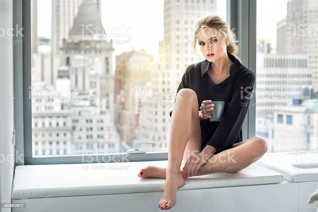 Beautiful woman drinking coffee at morning in luxury city penthouse stock photo