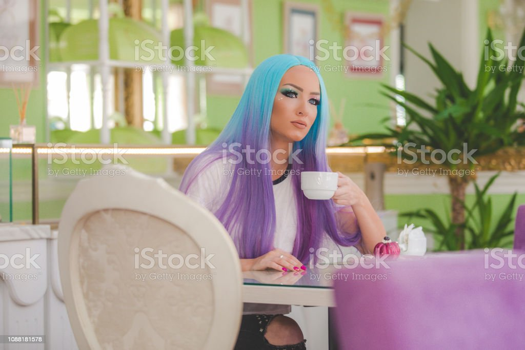Beautiful woman with blue-purple wig sitting in a candy store ,eating...