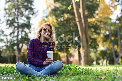 Young happy Woman in checkered shirt and blue jeans with toothy Smile and sunglasses. Blonde girl drinking coffee in park sitting on grass wearing casual clothes smiling