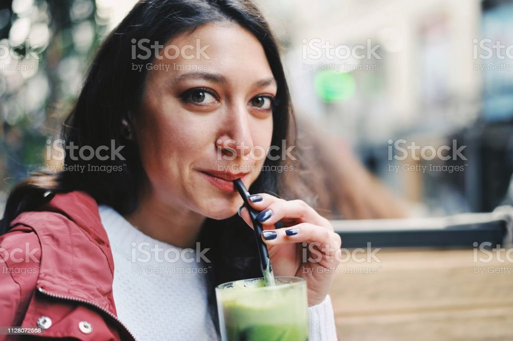 Beautiful woman drinking green juice stock photo