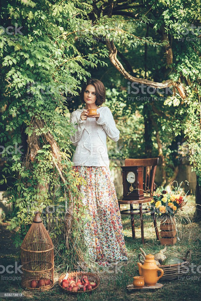 Beautiful woman drinking tea in a magical park stock photo