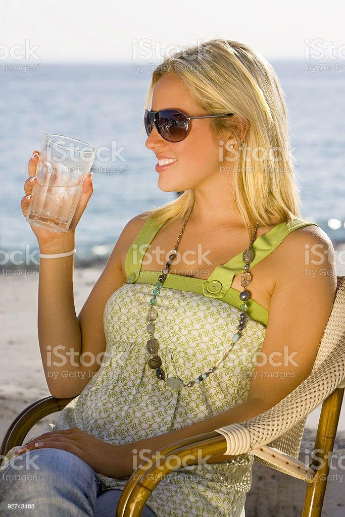 Schöne Frau trinkt Wasser am Strand In die Sonne am Abend Lizenzfreies stock-foto