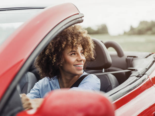 Beautiful woman driving a cabriolet car with safety seat belt on stock photo