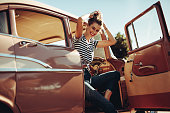 Attractive young female sitting in a car and tying her hair. Woman sitting on driving seat with door open.
