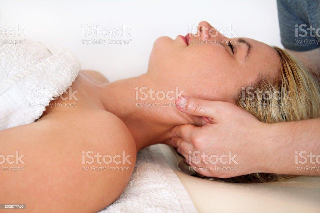 Mulher bonita durante e apreciando, receber uma massagem de bem-estar no centro de spa, ela é muito descontraída. Pescoço de recebimento mulher massagem no consultório médico. Procedimento de Osteopatia alongamento no pescoço. foto royalty-free