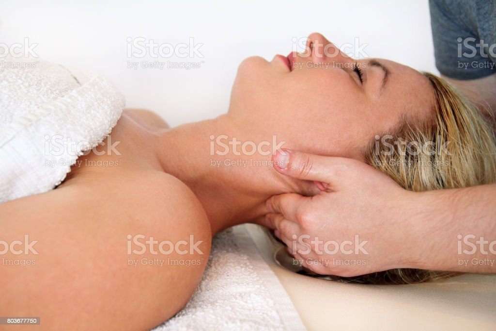 Beautiful woman during and enjoying, receiving a wellness neck massage in spa center, she is very relaxed. Woman receiving neck massage in medical office. Stretching osteopathy procedure in the neck. stock photo