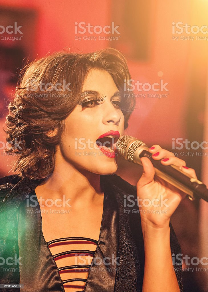 Beautiful woman during concert holding a microphone stock photo