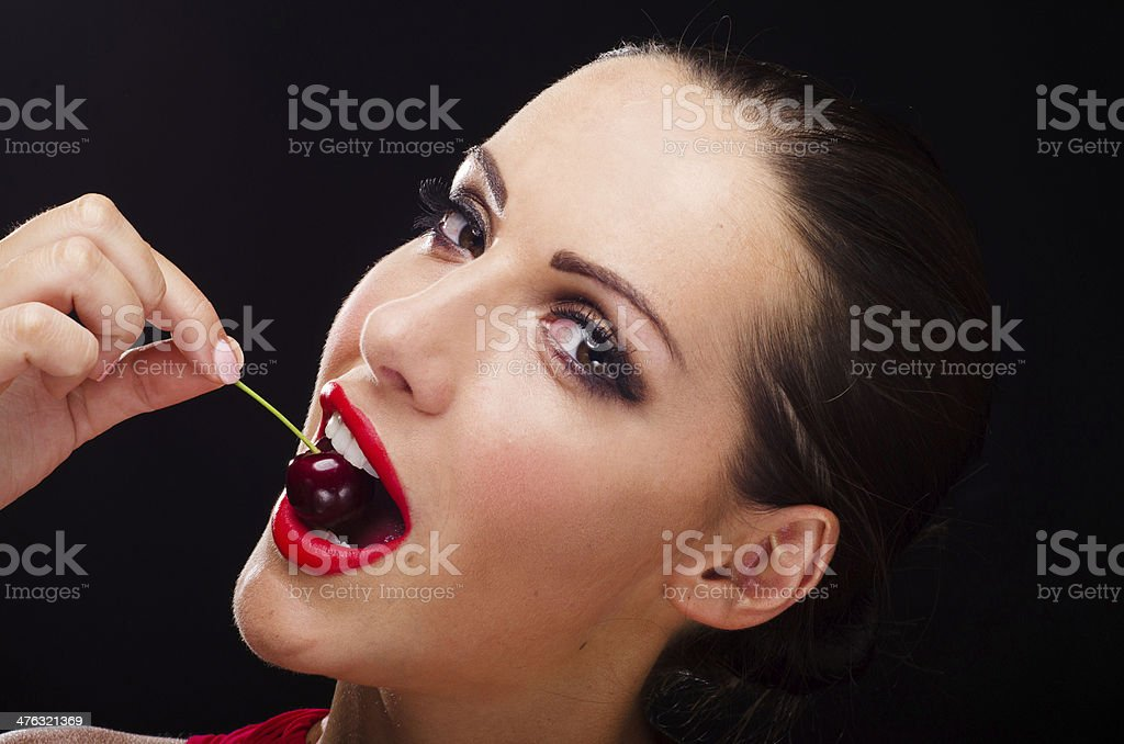 Beautiful woman eating a juicy cherry royalty-free stock photo