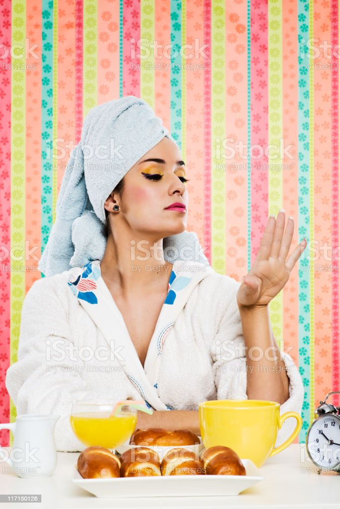 Beautiful woman eating breakfast while cheking her finger nails. royalty-free stock photo