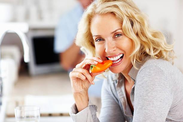 schöne frau essen capsicum mit blur mann im hintergrund - altes damenhaar stock-fotos und bilder