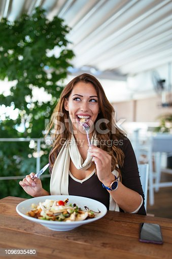 Portrait of happy woman eating fresh caesar salad at restaurant