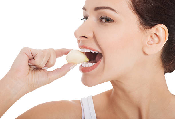 beautiful woman eating garlic. - garlic stock photos and pictures