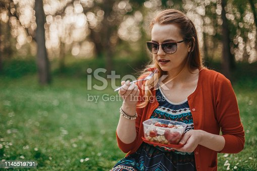 Young woman eating healthy vegetable salad at the picnic in nature