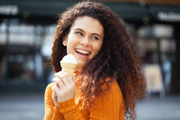 Beautiful woman eating ice-cream stock photo