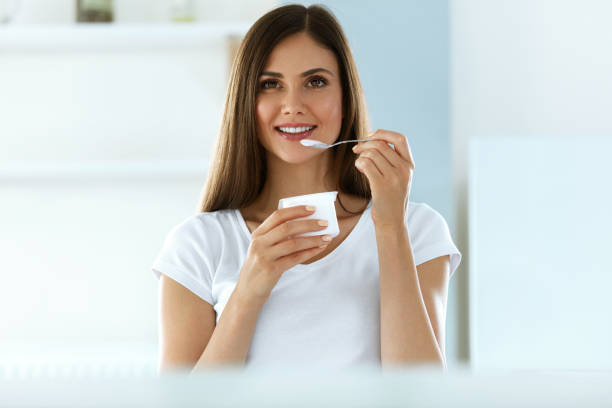 beautiful woman eating organic yogurt. healthy diet nutrition - yogurt stock pictures, royalty-free photos & images
