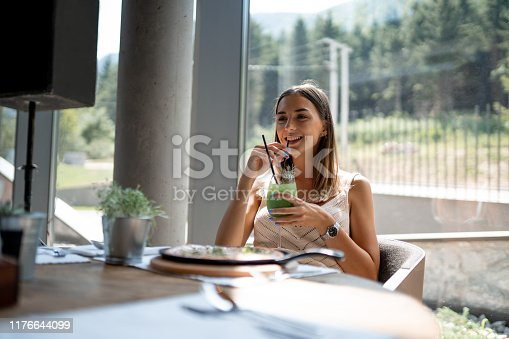 Beautiful woman eating pizza in restaurant