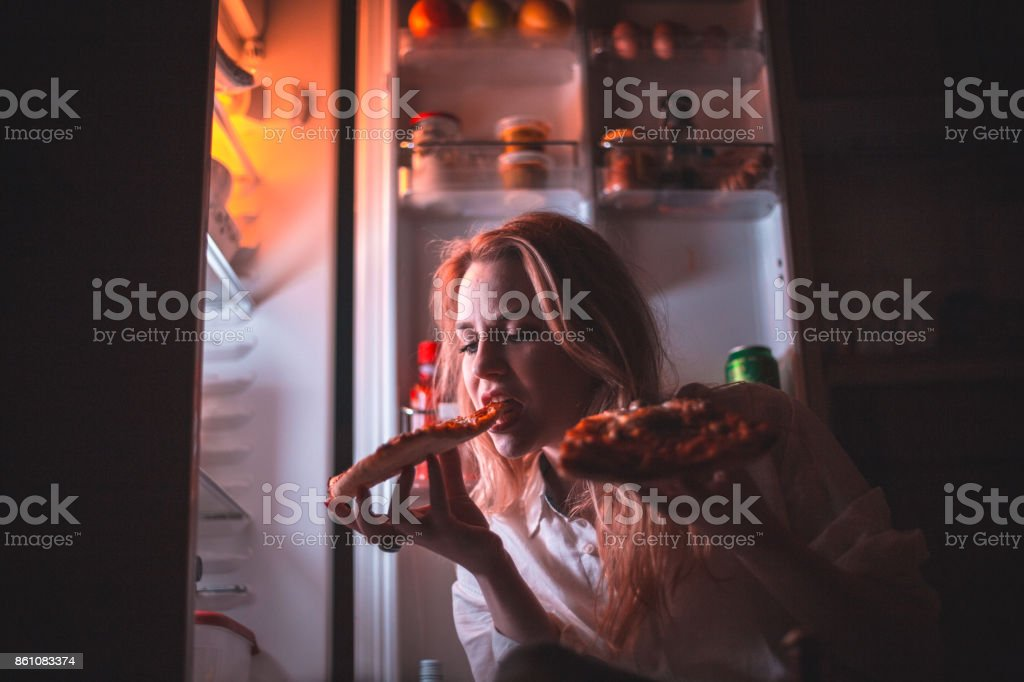 Beautiful woman eating pizza late night stock photo