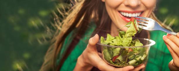 Beautiful woman eating salad stock photo