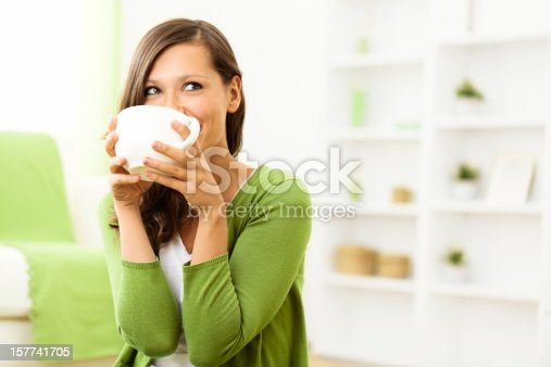 Beautiful woman enjoying a cup of coffee at home