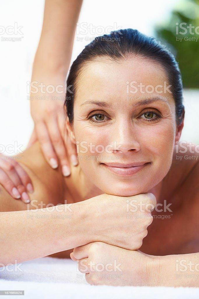 Beautiful woman enjoying a shoulder massage royalty-free stock photo