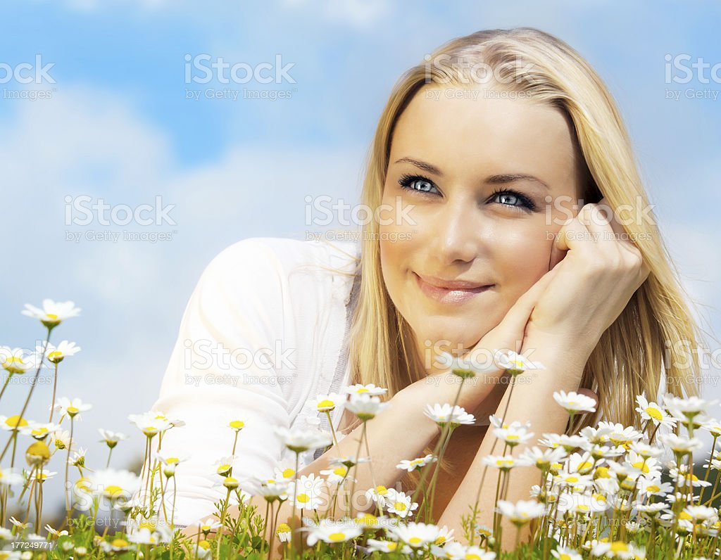 Beautiful woman enjoying daisy field and blue sky royalty-free stock photo
