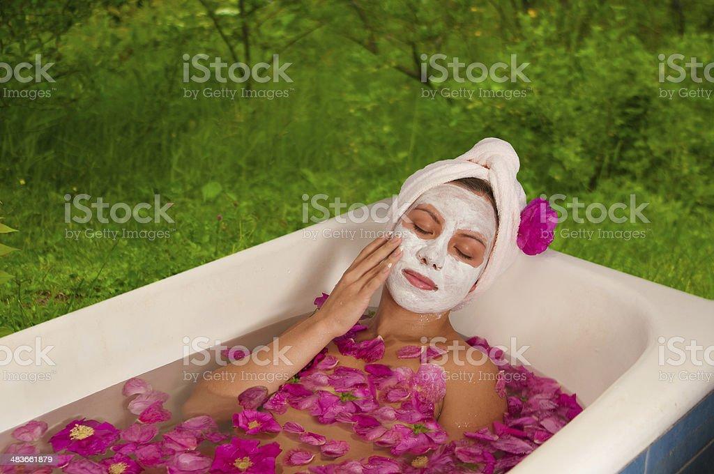 beautiful woman enjoying floral bath stock photo