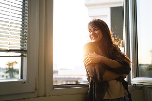 Beautiful young woman looking through the window while enjoying fresh air