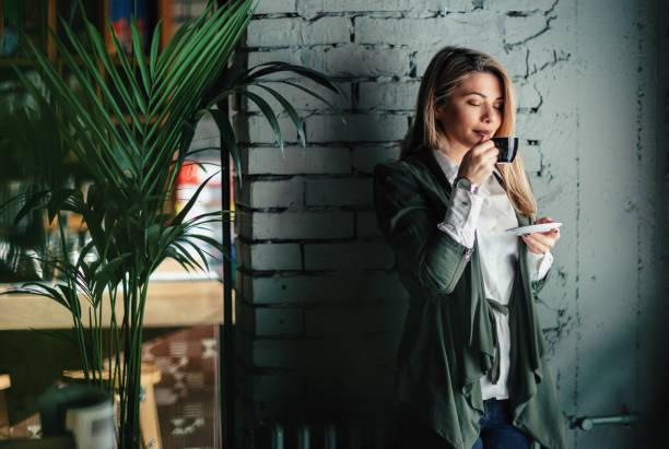 beautiful woman enjoying in smell of fresh coffee in a cafe. - эспрессо стоковые фото и изображения