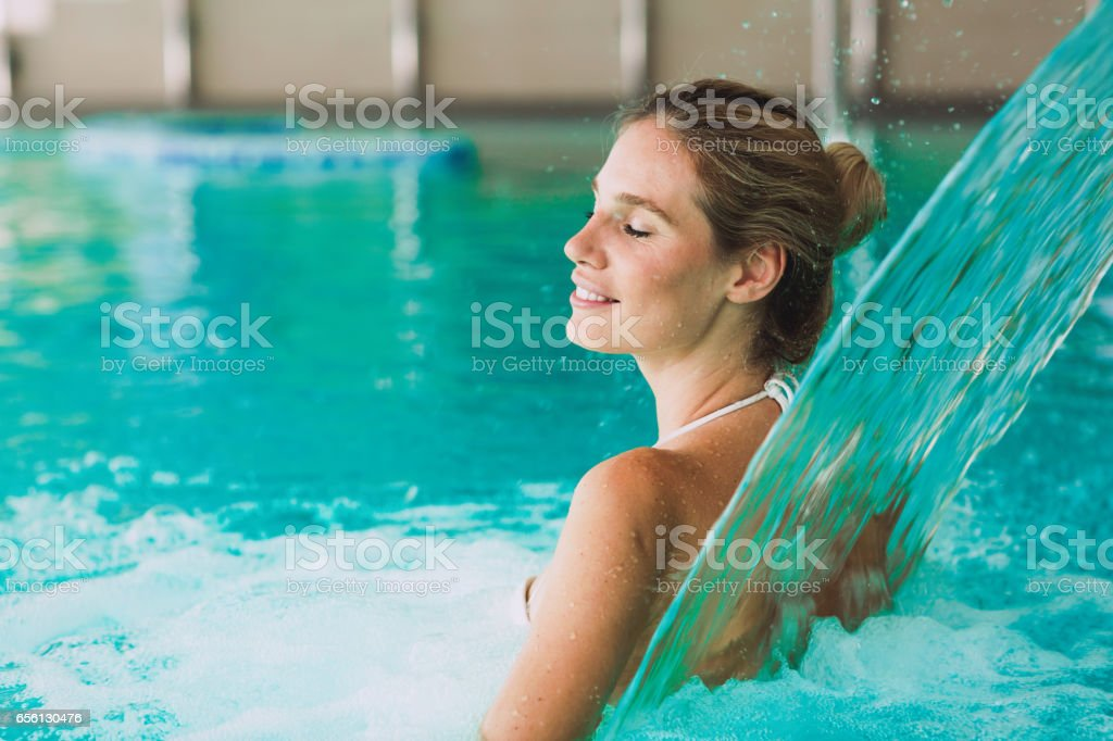 Beautiful woman enjoying jet of water in spa  resort stock photo