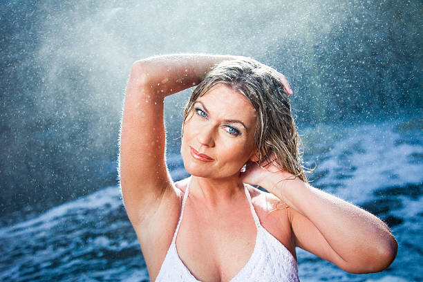 Beautiful woman enjoying near river waterfalls Portrait of beautiful woman enjoying of rest and harmony among sparkling water drops flying from river waterfalls in sunny summer morning goosebumps stock pictures, royalty-free photos & images