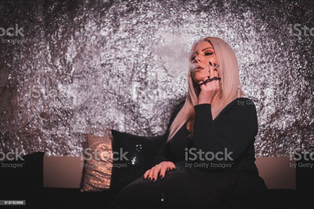 Beautiful woman enjoying night out and smoking a cigarette stock photo