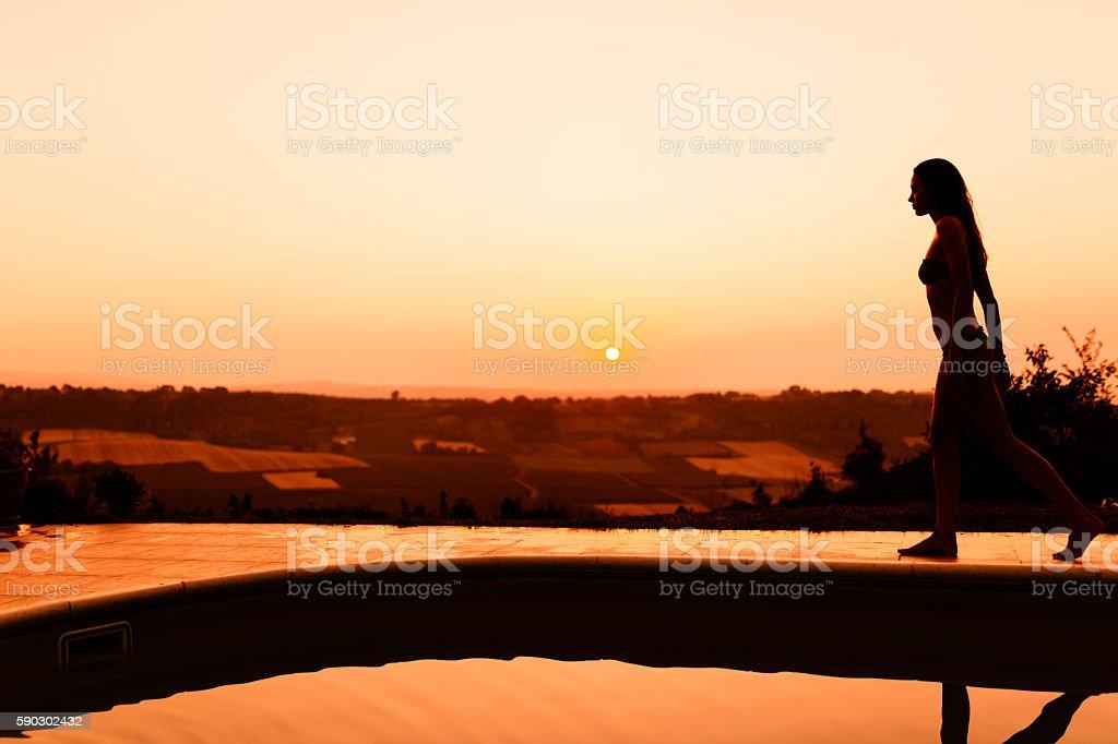 Beautiful woman enjoying summer by her pool royaltyfri bildbanksbilder