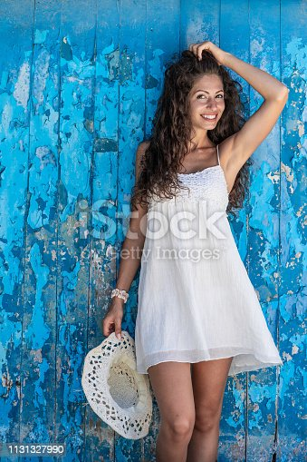 Woman enjoying summer vacations, standing hands up in front of old blue wooden wall.