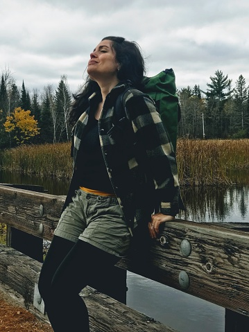 Beautiful woman enjoying the outdoors and hiking in nature. The woman is dressed for the outdoors in flannel with gold, green, and black tones, wearing a hiking backpack and showing confidence in her ability to go out and adventure, near her home, but alone in nature spending time to recharge her inner-self. Taken in the fall in Northern Wisconsin. Autumn tones in the surrounding forests near the road and bridge she is hiking on.