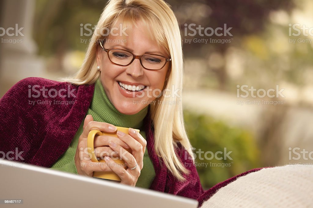 Beautiful Woman Enjoys Her Warm Drink and Laptop royalty-free stock photo
