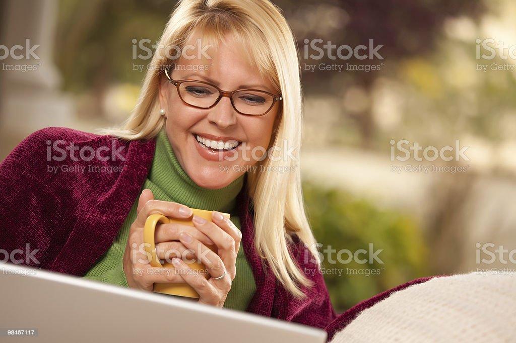 발코니에서 아름다운 여자 자신의 따뜻한 음료 및 랩탑형 royalty-free 스톡 사진