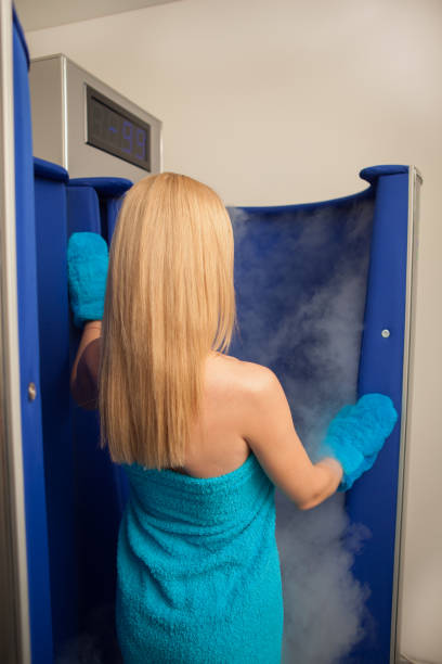Beautiful woman entering cryo sauna at beauty spa center Vertical rear view shot of a blond haired woman wrapped in blue towel entering steaming cryosauna booth at beauty clinic. Woman receiving cryotherapy treatment at medical center. Health, skincare concept cryotherapy stock pictures, royalty-free photos & images