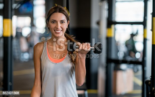 Portrait of a beautiful woman exercising at the gym lifting free-weights and looking at the camera smiling