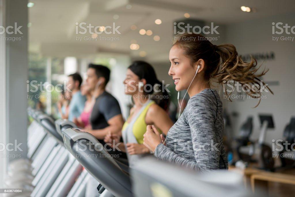 Belle femme exerçant à la salle de gym en cours d'exécution sur un tapis roulant - Photo
