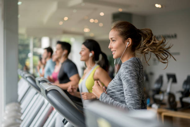 beautiful woman exercising at the gym running on a treadmill - health club stock photos and pictures