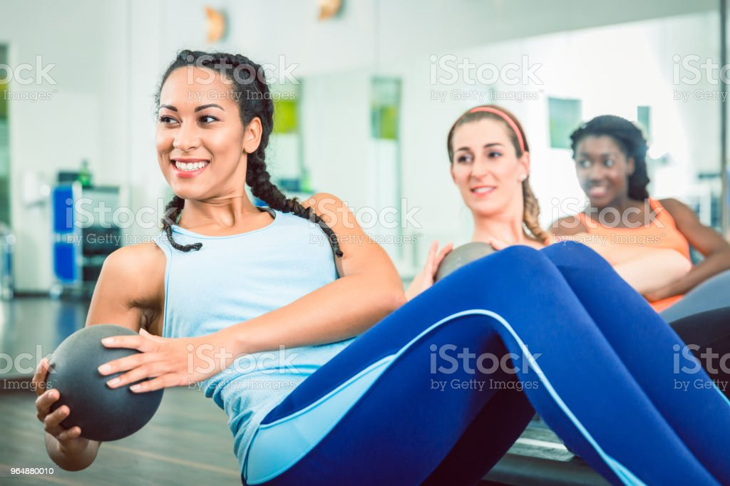 Beautiful woman exercising Russian twist with med ball for strong abs at the gym stock photo