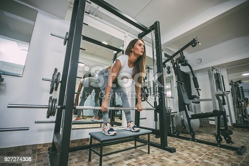 670937518istockphoto Beautiful woman exercising with barbell in the gym 927274308