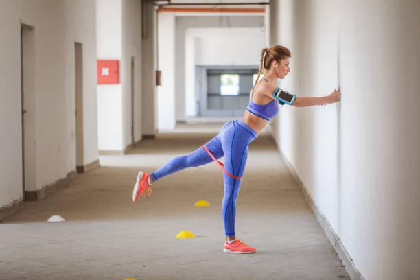 schöne frau, die das training mit gummiband - armband i gummi stock-fotos und bilder