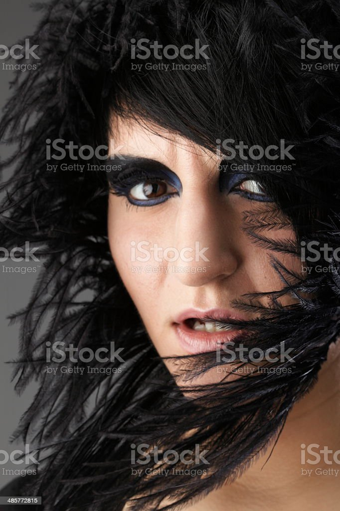 Beautiful woman face in black feather royalty-free stock photo