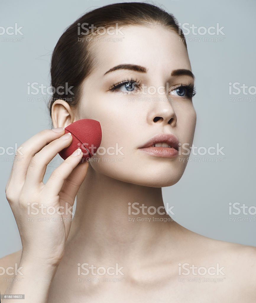 Beautiful woman face. Perfect makeup. Skincare foundation. Spong stock photo